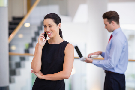 company premises: Businesswoman talking on mobile phone at conference centre