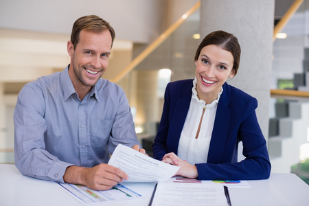 company premises: Portrait of businesswoman working at desk with colleague in conference centre