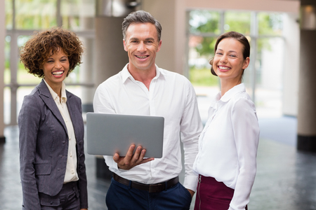 company premises: Portrait of business executives holding laptop and laughing at conference centre