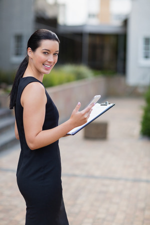 premises: Portrait of businesswoman holding mobile phone and clipboard outside the conference centre