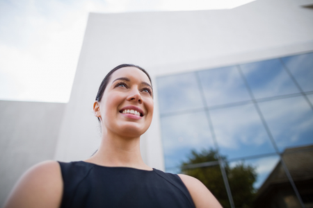 premises: Low angle view of a beautiful businesswoman smiling