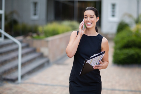 company premises: Businesswoman holding clipboard and talking on mobile phone outside the conference centre Stock Photo