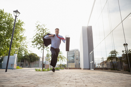 conference centre: Businessman holding briefcase running outside the conference centre