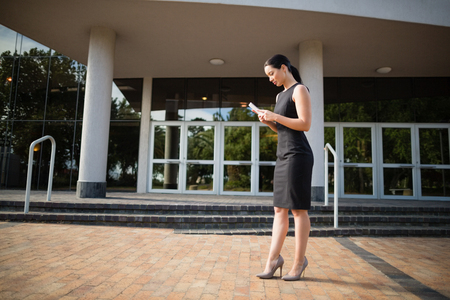 conference centre: Businesswoman using mobile phone outside the conference centre