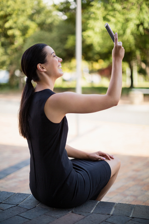 company premises: Happy businesswoman taking a selfie on mobile phone outside the conference centre Stock Photo