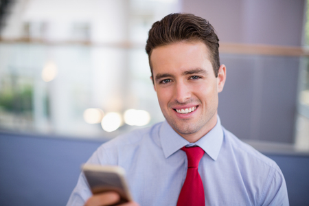 premises: Close-up of businessman holding mobile phone at conference centre Stock Photo