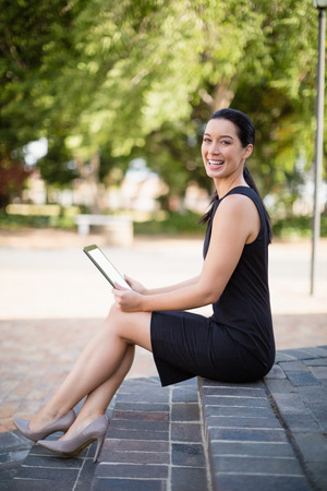 premises: Happy businesswoman holding digital tablet outside the conference centre