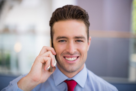 conference centre: Portrait of businessman talking on mobile phone at conference centre Stock Photo