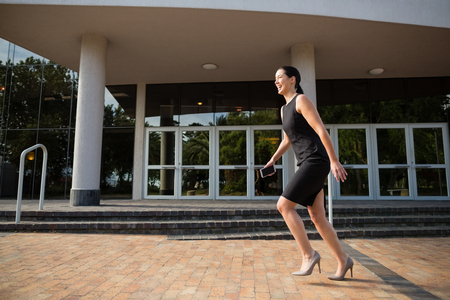 conference centre: Cheerful businesswoman running outside the conference centre