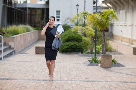 Businesswoman holding clipboard and talking on mobile phone outside the conference centre Stock Photo