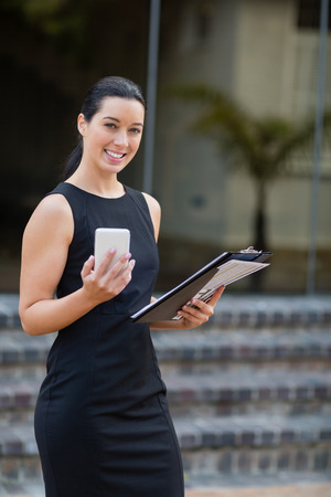 Portrait of businesswoman holding mobile phone and clipboard outside the conference centre