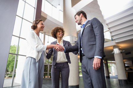 company premises: Business executives shaking hands with each other at conference centre
