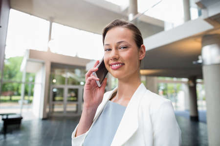 premises: Portrait of a happy businesswoman talking on mobile phone at conference centre Stock Photo
