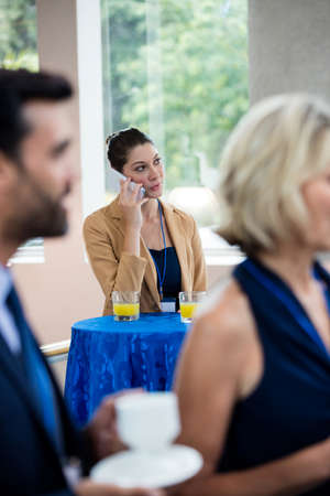 Female business executive talking on mobile phone at conference center Stock Photo