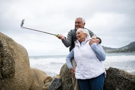 Senior couple taking a selfie from selfie stick on beach