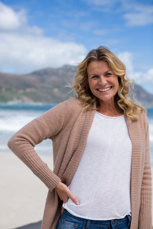 Portrait of mature woman with hands behind head standing on the beach