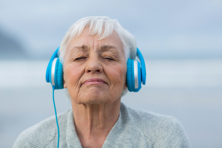 Close-up of senior woman listening to music on headphones Stock Photo