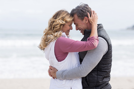 embracing couple: Romantic mature couple embracing each other on the beach Stock Photo