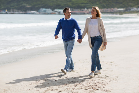 holding hands while walking: Mature couple holding hands while walking on the beach