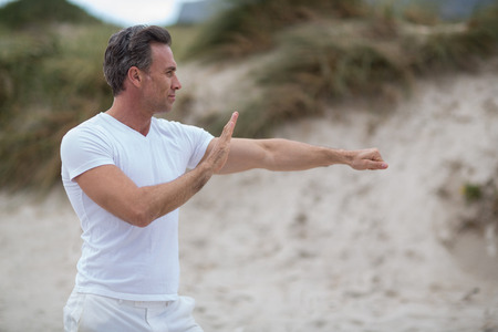 Mature man doing exercise on the beach Stock Photo