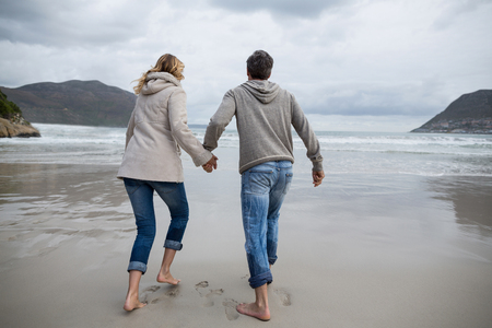 Rear view of mature couple running on the beach