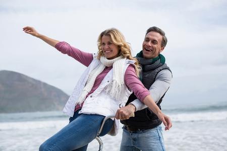 해변에서 행복한 성숙한 커플 승마 자전거 스톡 콘텐츠