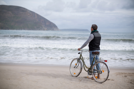 Rear view of mature man standing with bicycle on the beach