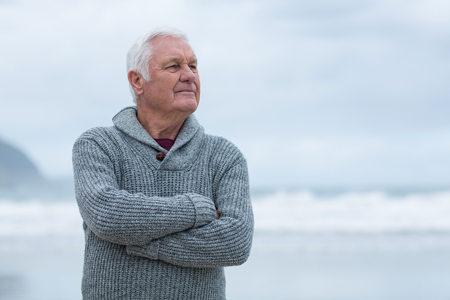 Smiling senior man standing with arms crossed on the beach Stock Photo