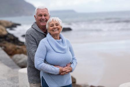 Gelukkig hoger paar die elkaar op het strand omhelzen Stockfoto