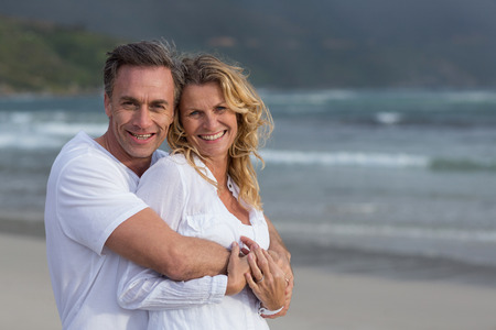 Romantic mature couple embracing each other on the beach Stock Photo