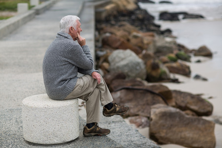 Senior man sitting on the steps near beach