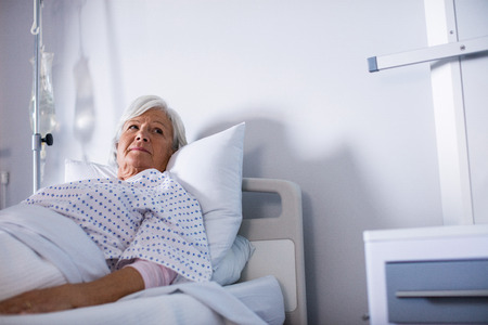 Thoughtful senior woman lying on bed in hospital
