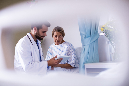 Male doctor showing digital tablet to female senior patient in the ward Stock Photo