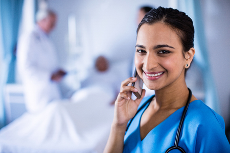 Smiling female doctor talking on a mobile phone in the hospital Stock Photo