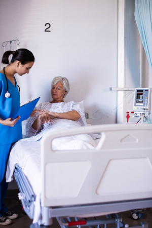 ageing process: Female doctor examining senior woman in the ward at hospital Stock Photo