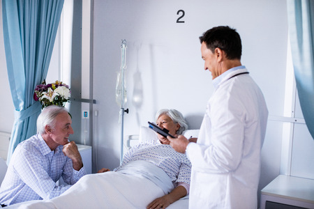 Senior patient interacting with doctor in hospital Stock Photo