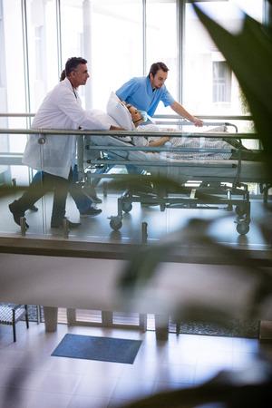 paciente en camilla: Equipo de médicos que toman mujer embarazada a quirófano en el hospital