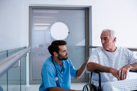health professionals: Doctor interacting with male senior patient on a wheelchair in the passageway