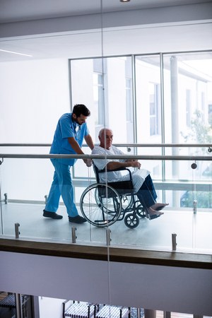 ageing process: Male doctor interacting with male senior patient in the passageway at hospital