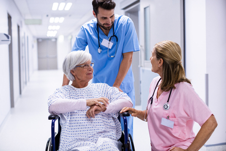 Male and female doctor interacting with female senior patient on wheelchair in corridor at hospital