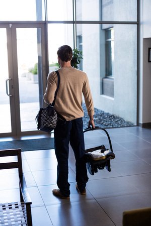 Rear view of man leaving the hospital with baby