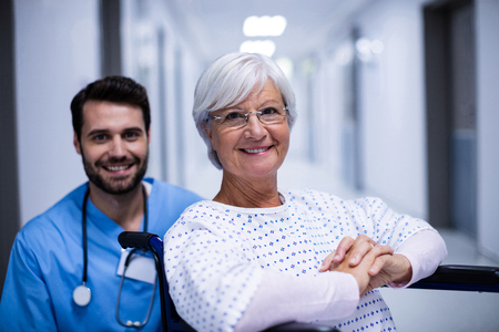 Portrait of male doctor and female senior patient smiling in the corridor at hospital Stock Photo
