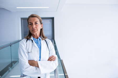 Portrait of female doctor standing with arms crossed in the passageway at hospital