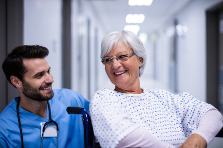 Male doctor interacting with senior patient on wheel chair in the corridor at hospital Stock Photo
