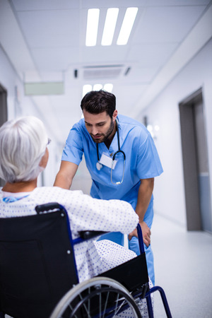 Male doctor interacting with senior patient on wheelchair in the corridor Stock Photo