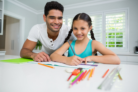 Portrait of father assisting her daughter in doing her homework at home