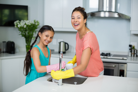 domicile: Portrait of mother assisting her daughter in cleaning vessel at home