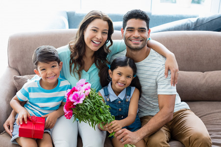 Portrait of parents and kids sitting on sofa with present in living room at home
