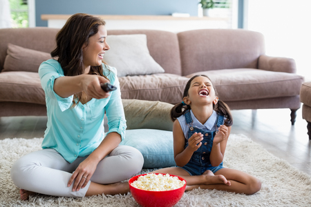 Mother and daughter watching television while having popcorn in living room at home Фото со стока