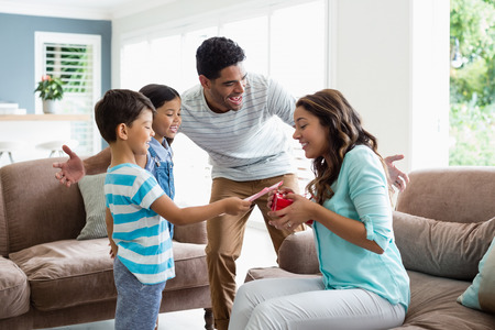 Mother receiving a gift from his kids and husband in living room at home